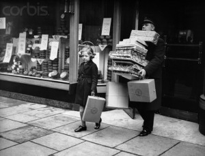 1936 --- A man carries a pile of presents purchased by a young girl during a Christmas shopping expedition. --- Image by © Hulton-Deutsch Collection/CORBIS